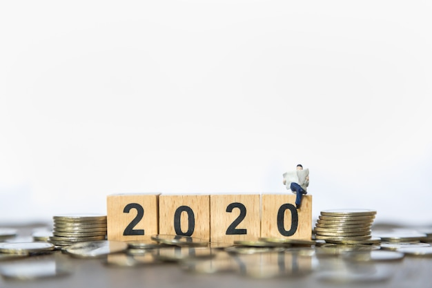 2020 new year  business, money and planning concept. close up of businessman miniature read a newspaper o Premium Photo