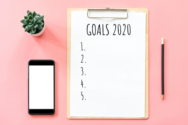 2020 new year concept. goals list in stationery, blank clipboard, smartphone, pot plant on pink pastel color with copy space Premium Photo