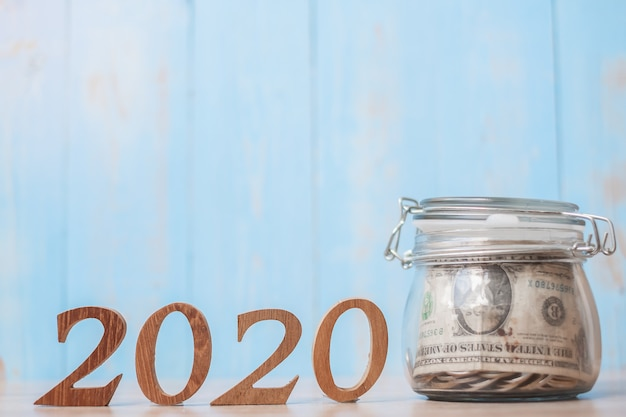 2020 new year with money glass jar and wooden number. Premium Photo