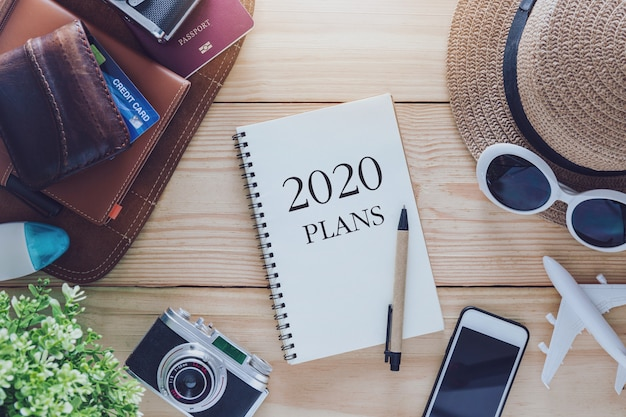2020 note book plans with hat, sunglasses, phone, camera and aeroplane Premium Photo