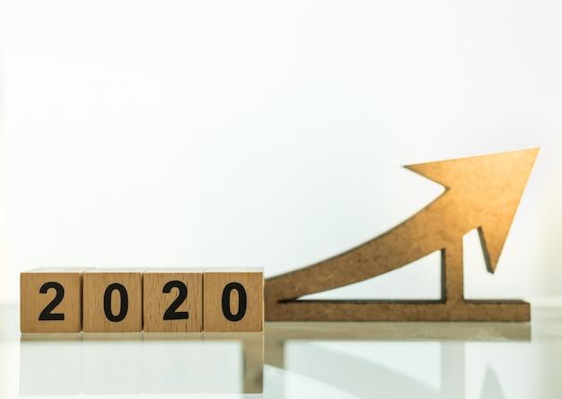 Концепция планирования, бизнеса и целей 2020 года. закройте вверх деревянных блоков номера с деревянным diecut значка стрелки с космосом экземпляра. Premium Фотографии