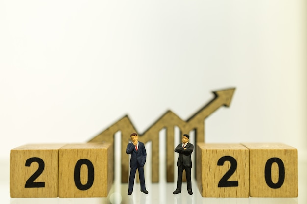 2020 planning,  business and goal concept. close up of two businessman miniature figure people standing Premium Photo