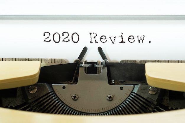 2020 review word typed on a yellow vintage typewriter. Premium Photo