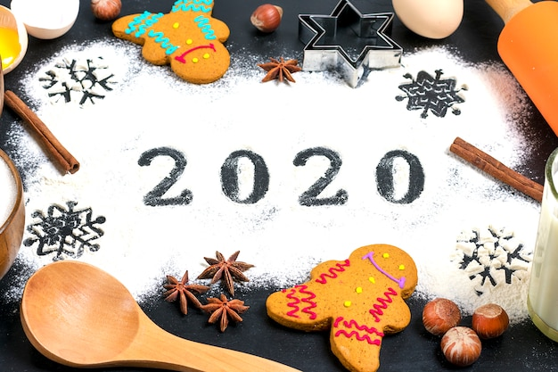2020 text made with flour with decorations on a black background. Premium Photo