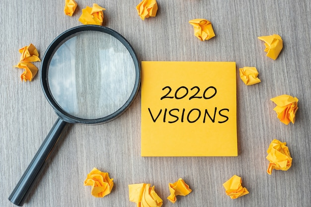 2020 visions words on yellow note with crumbled paper Premium Photo