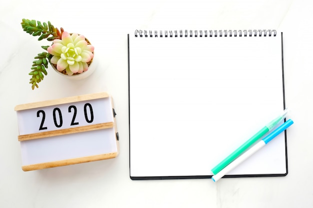 2020 on wood box blank notebook paper on white marble table background Premium Photo