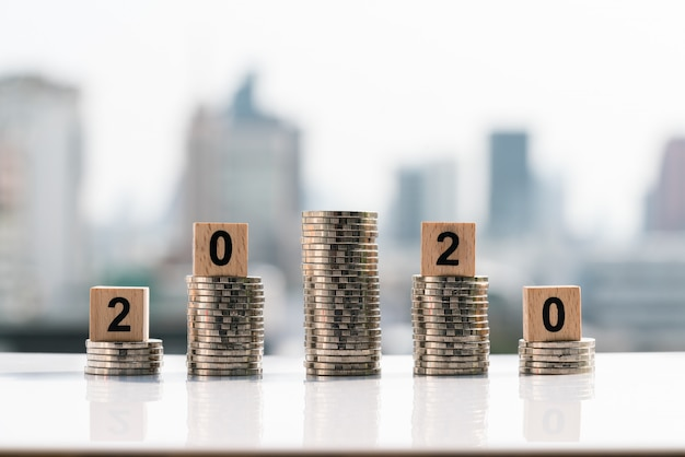2020 wooden blocks on top of coin stack on city backgrounds. Premium Photo
