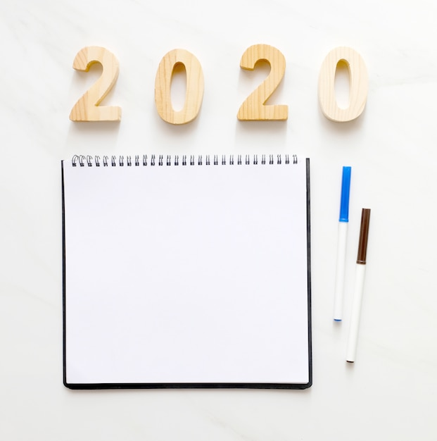 2020 wooden letters and blank notebook paper with copy space for text new year background banner concept Premium Photo