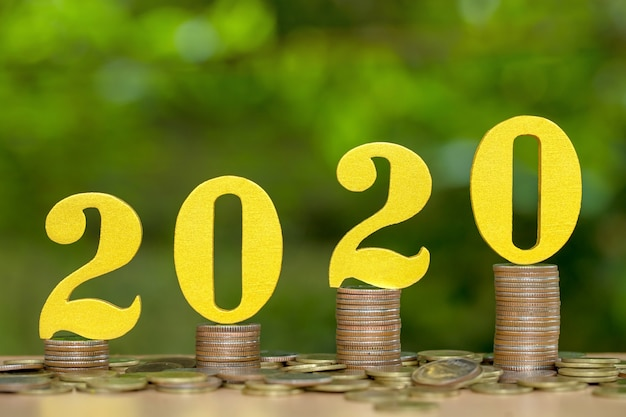 2020 wooden numbers on coins stacked showing financial growth, saving money Premium Photo