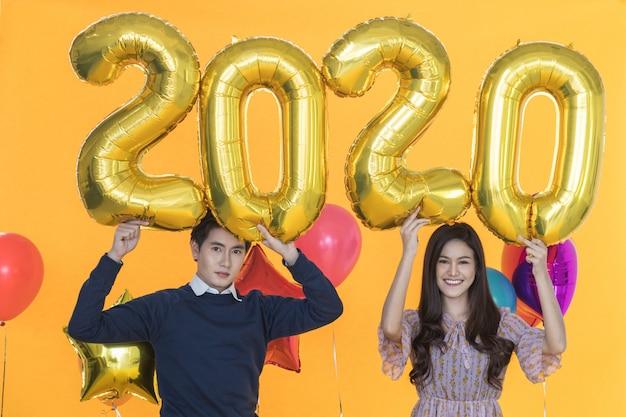 2020年の新年コンセプト。笑顔の美しい若いアジア女性とゴールデンナンバーバルーンとカラフルなバルーンパーティーを保持しているスマートな男の肖像 Premium写真