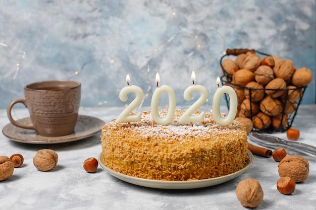 Морковный торт с 2020 свечами и чашкой чая на сером бетоне Бесплатные Фотографии