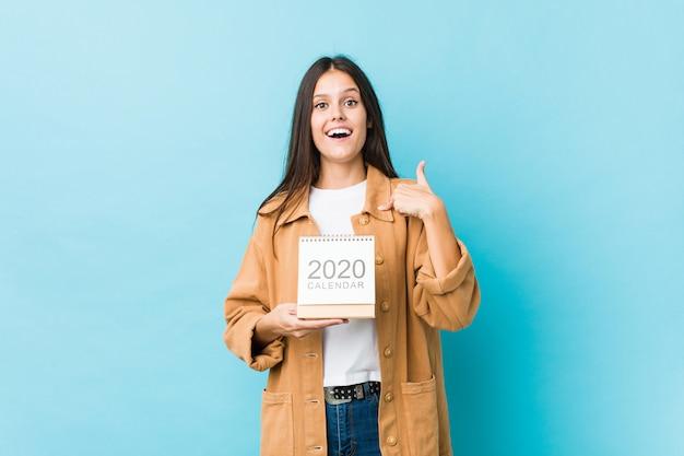Молодая женщина кавказской, проведение 2020-х годов календарь удивлен, указывая на себя, широко улыбаясь. Premium Фотографии