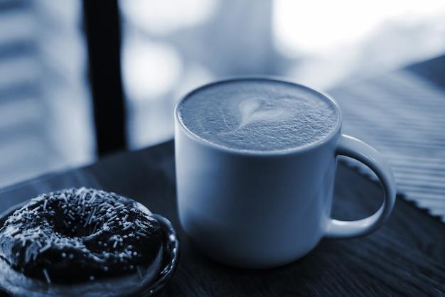 Кофе с нарисованным сердцем и молоко на деревянном столе в кофе. цвет концепции 2020 года. закройте пончик с россыпью на столе рядом с кофе Premium Фотографии