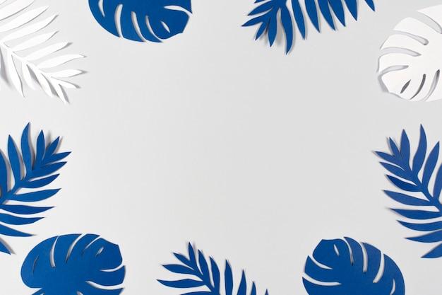 灰色の背景に熱帯紙を残します。 2020年の色-クラシックブルー。 Premium写真