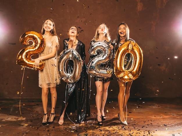 金と銀の2020年風船を保持しているスタイリッシュなセクシーなパーティードレスで幸せな豪華な女の子 無料写真