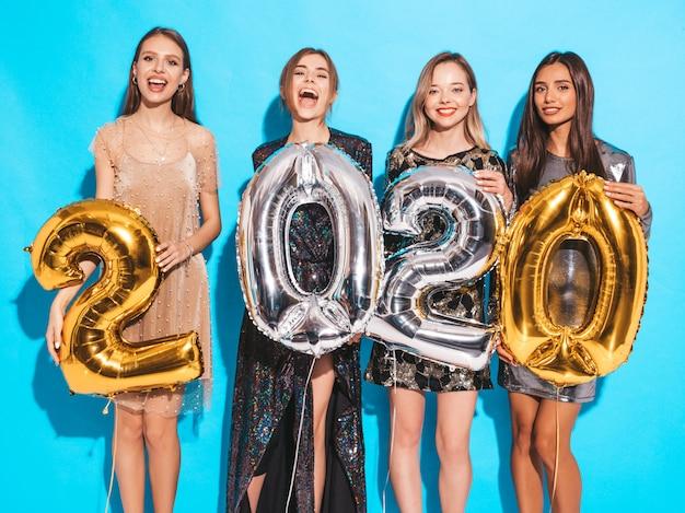 Счастливые великолепные девушки в стильных сексуальных платьях для вечеринок с золотыми и серебряными воздушными шарами 2020 года Бесплатные Фотографии