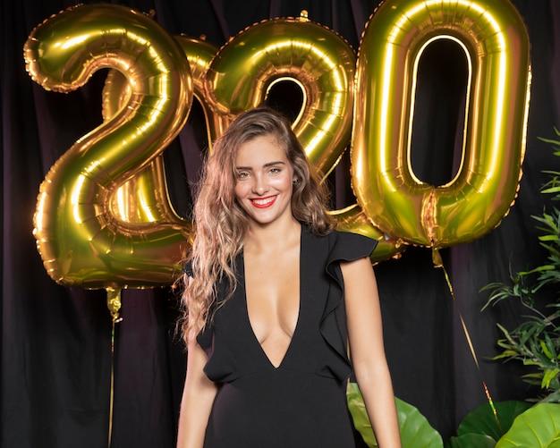 Красивая девушка улыбается с 2020 года новогодние шары Бесплатные Фотографии
