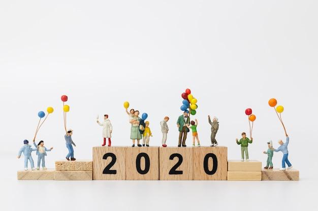 ミニチュアの人々:木製ブロック番号2020にバルーンを保持している幸せな家族 Premium写真