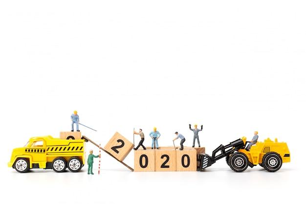 ミニチュアの人々:労働者チームは木製のブロック番号2020を作成します Premium写真