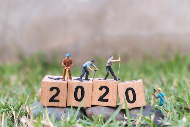 ミニチュアの人々、労働者チームは木製のブロック番号2020を作成します Premium写真