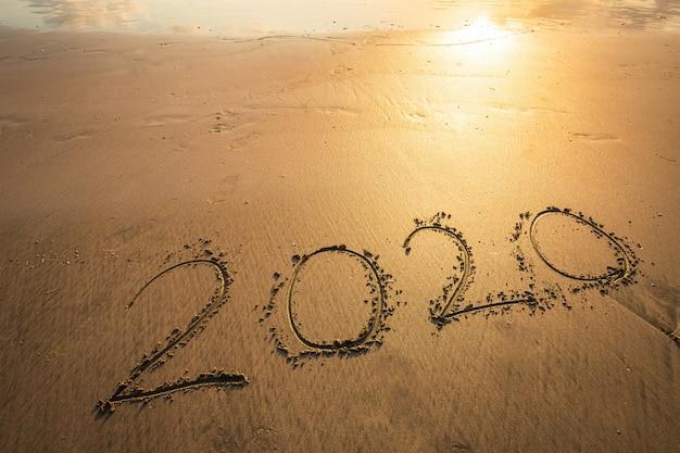 地平線上の波早朝日の出と美しい海のビーチで幸せな新年2020年テキスト Premium写真
