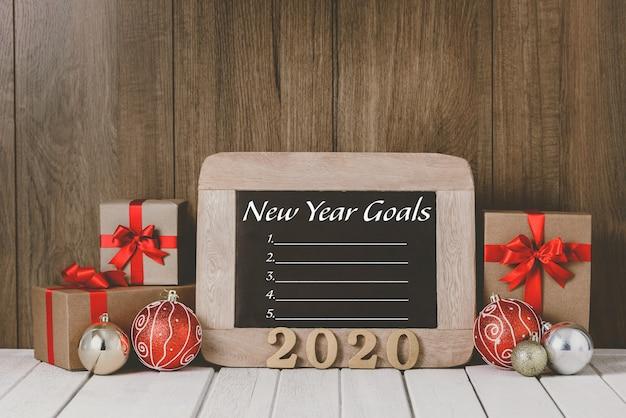 2020 деревянный текст и рождественские украшения и список новогодних целей написано на доске над деревянным Premium Фотографии