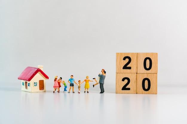 Миниатюрная семья с мини-домом и деревянными блоками 2020 года Premium Фотографии