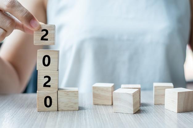 2020年の言葉で木製キューブを持つビジネス女性の手 Premium写真