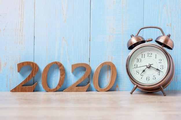 2020新年あけましておめでとうございます、レトロな目覚まし時計と木製の番号。 Premium写真
