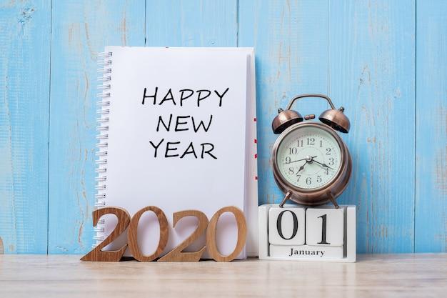 2020新年あけましておめでとうございます、ノートブック、レトロな目覚まし時計、木製の番号。 Premium写真