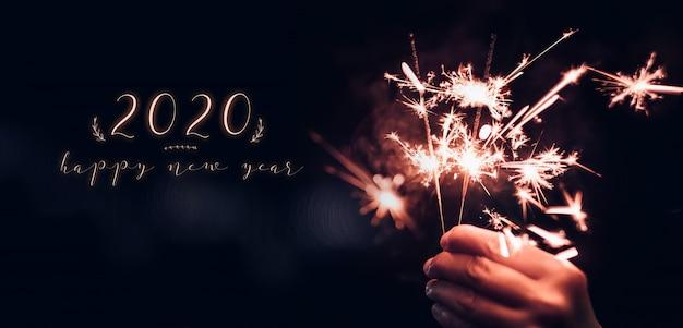 線香花火の花火の爆発を持っている手で幸せな新年2020 Premium写真