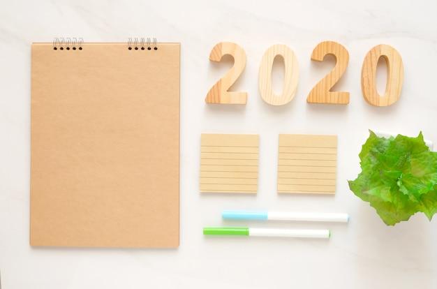 2020年の木製の手紙とテキスト新年背景バナーコンセプトのコピースペースを持つ空白のノートブック紙 Premium写真