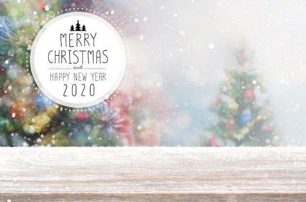 空の木製テーブルの上にクリスマスと新年あけましておめでとうございます2020は、降雪でボケクリスマスツリー背景をぼかします。 Premium写真