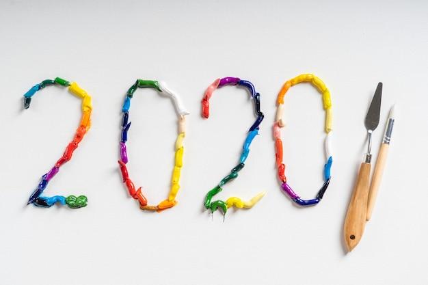 Номер 2020 написан на белом холсте яркими масляными красками. вид сверху крупным планом. Premium Фотографии