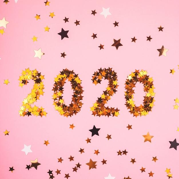 ピンクの背景の金の紙吹雪の2020年新年のシンボル。 Premium写真