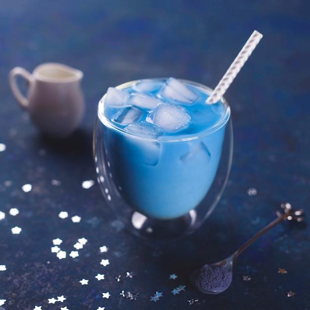 青いテーブルの上のグラスに氷と抹茶ブルーティー。 2020年の色。 Premium写真