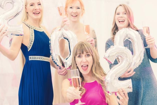 シャンパンで新年を祝う女性2020 Premium写真