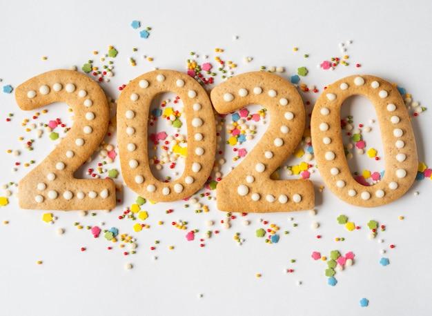 Разноцветная выпечка сахарного топинга и пряник в виде цифр 2020 на белом фоне Premium Фотографии