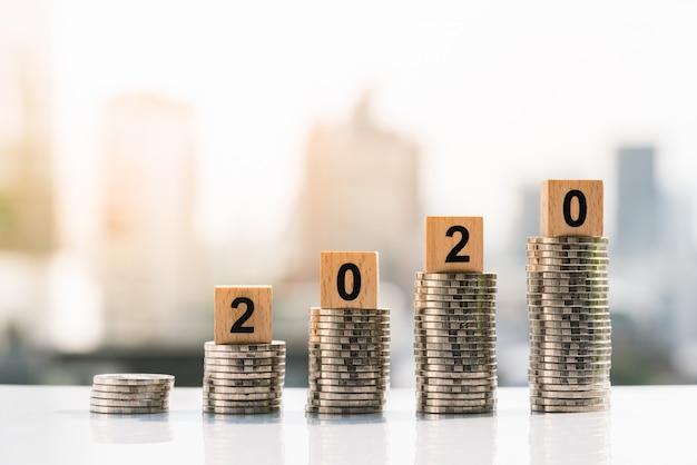 2020 деревянных блоков на вершине стека монет на фоне города. Premium Фотографии