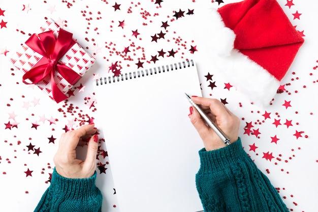 Женщина в зеленом свитере пишет контрольный список планов и мечтаний на следующий год. список пожеланий на рождество и новый год. список дел на новый 2020 год с красным праздничным декором. Premium Фотографии