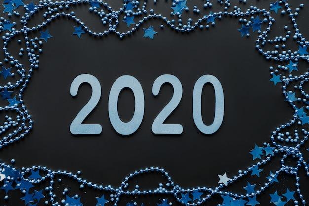 カラークラシックブルーの新しい2020年。青い装飾の境界線、輝く星と黒の背景にビーズ。明けましておめでとうございます。クリスマスパーティー。フラット横たわっていた。上面図。クリスマス。 Premium写真