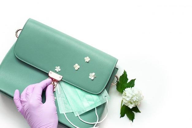 医療用マスク、消毒剤、手袋が入った女性用バッグ。 2020年春夏のコンセプトがコロナウイルスの世界的流行から脱却します。 Premium写真