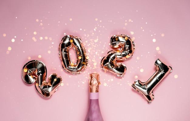 2021 золотая фольга с воздушными шарами с розовым шампанским и боке. верхний горизонтальный вид копией пространства новый год и концепция праздника Premium Фотографии