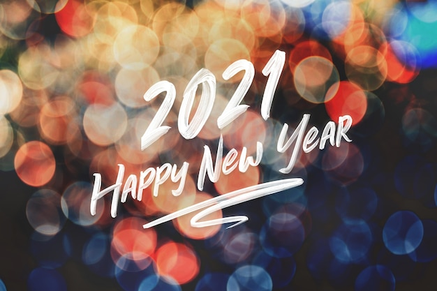 2021 happy new year brush stroke handwriting on abstract festive colorful bokeh light Premium Photo