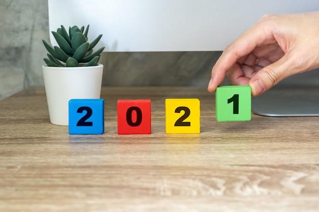 С новым годом 2021, рука держит деревянный блок на настольном компьютере деревянного стола и горшечном растении. новогодняя концепция Premium Фотографии