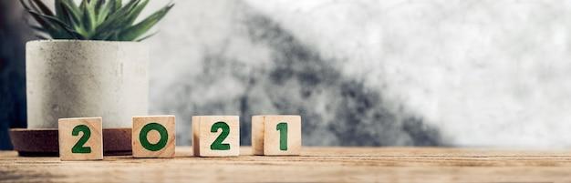С новым годом 2021 года на деревянном блоке на деревянном столе и бетонной стене с солнечным светом из окна Premium Фотографии