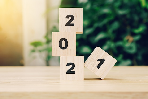 2021 happy new year on wood block on wood table with sunlight. new year concept. Premium Photo