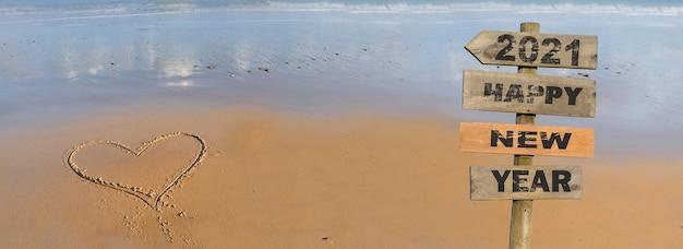 С новым годом 2021 писать на деревянном знаке на пляже с сердцем, рисующим на песке Premium Фотографии