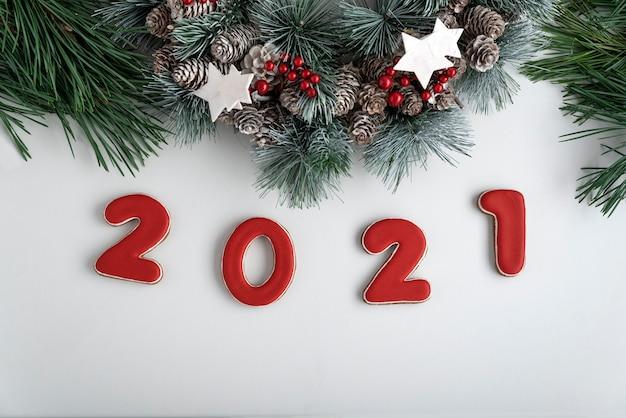 2021年の碑文とクリスマスリース、上面図。白色の背景。明けましておめでとうございます2021。 Premium写真