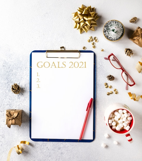 2021 new year goals. christmas decorations  with wish list text on notepad. flat lay Premium Photo